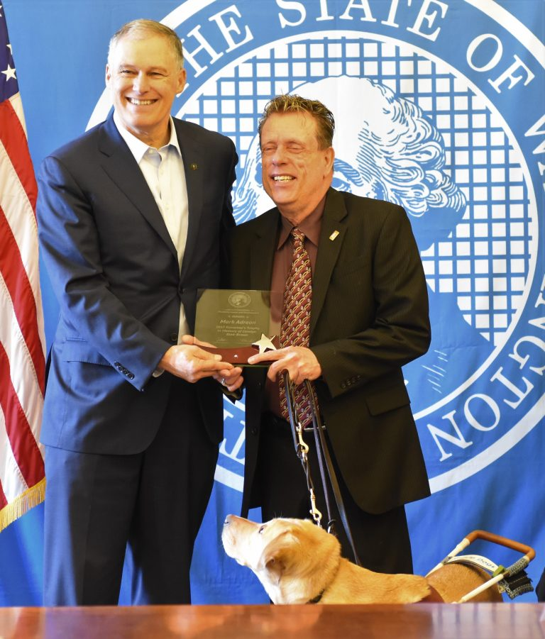 Mark Adreon receives the Governor's Trophy from Jay Inslee